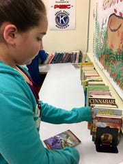 Sixth-grader Natalie McCollum chooses a book at the
