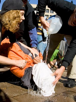 Protesters demonstrate the use of waterboarding on a volunteer in Washington in 2007.