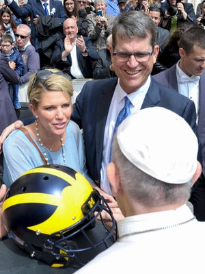 Pope Francis receives a helmet from Michigan coach Jim Harbaugh and his wife Sarah Harbaugh on April 26, 2017 during the Pontiff weekly audience at the Vatican.