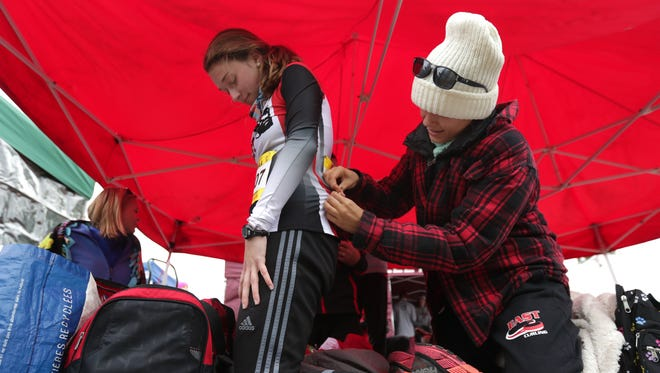 Eliza Morgan, right, helps Wausau East senior runner Mariah Haight pin her bib on before the statrt of the WIAA state cross country meet in October. Haight signed a national letter of intent with Augustana University on Wednesday afternoon.