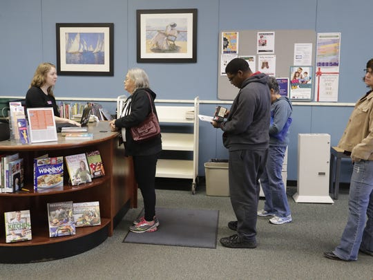 Jennifer Lorge, a library service associate, waits on a line of patrons at the East Branch of the Brown County Library on Main Street in Green Bay.
