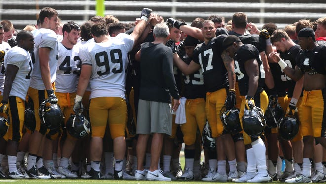 Members of the Iowa Hawkeye football program gather to talk things over with coach Kirk Ferentz following the Iowa Hawkeyes football practice at Kinnick Stadium on Saturday, Aug. 15, 2015, in Iowa City.