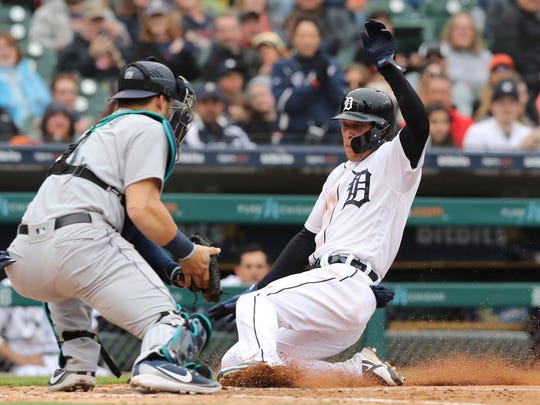 Detroit Tigers' JaCoby Jones safely beats the throw to Seattle Mariners catcher Mike Zunino and scores during the sixth inning of game one of a baseball doubleheader, Saturday, May 12, 2018, in Detroit. (AP Photo/Carlos Osorio)