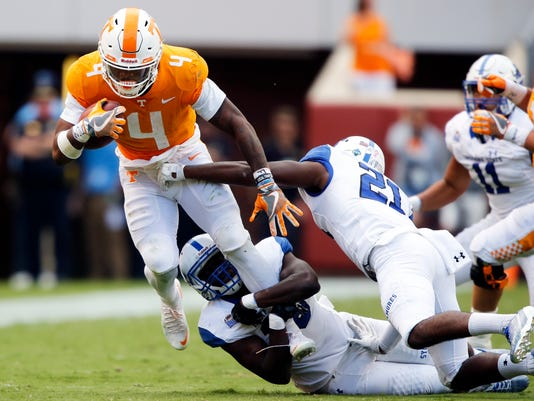 Tennessee running back John Kelly (4) tries to escape the grasp of Indiana State linebacker Jonas Griffith (46) and safety De'Jaun Tyson (21) in the second half of an NCAA college football game, Saturday, Sept. 9, 2017, in Knoxville, Tenn. Tennessee won 42-7. (AP Photo/Wade Payne)