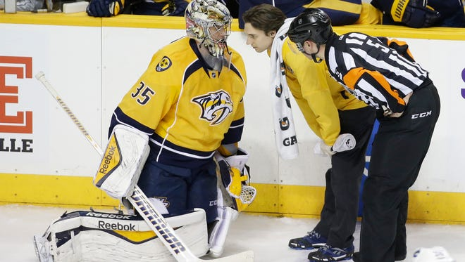 Nashville Predators goalie Pekka Rinne (35), of Finland, is tended to alter a collision against the Vancouver Canucks in the third period of an NHL hockey game Tuesday, Jan. 13, 2015, in Nashville, Tenn. Rinne left the ice and was replaced after the play. (AP Photo/Mark Humphrey)