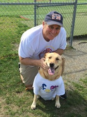 Kent Calhoun of Hopewell Junction and his dog, Buddy, take in the games at Arlington High School during its Friends of Jaclyn Day