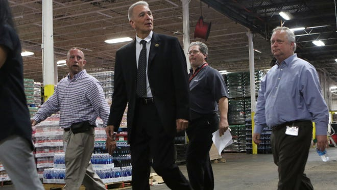 Rep. Ralph Abraham, R-Alto, walks with Robert Kuntz, left, Jerry Lawrence, center, and Keith Biedenharn, right, who are all members of the Monroe Coca-Cola Bottling Co.'s leadership during a tour of the facility on Wednesday.