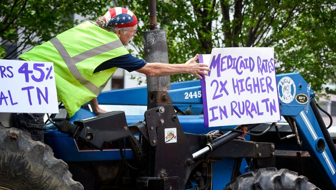 Allen Rubin presses a protest sign on a tractor as they prepare to ride around the block in front of the Estes Kefauver Federal Building and Courthouse to protest healthcare in Nashville, Tenn., Thursday, July 6, 2017.