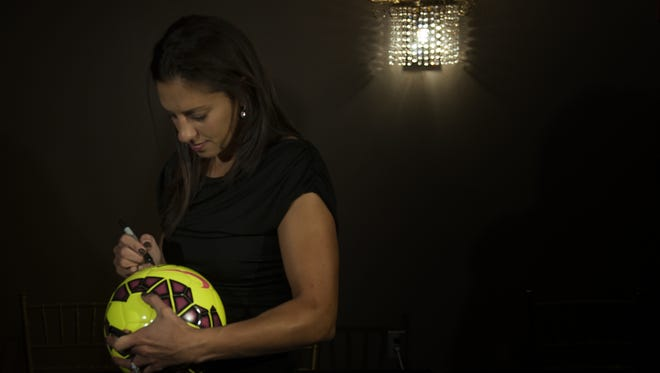 Delran native Carli Lloyd autographs a ball during the Philadelphia Sports Writers Association dinner Monday night at the Crowne Plaza Hotel in Cherry Hill.