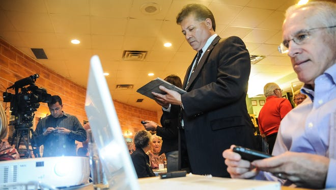 Mayor Ken Miyagishima, center, and his campaign manager Don Kurtz keep their eyes glued to tablets, phones and laptops on Tuesday at Los Compas Restaurant as the numbers are calculated during the 2015 municipal election. Miyagishima was elected to a third term as mayor.
