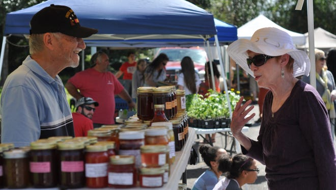 Steve Saia (left) talks with a customer Thursday at the Pineville Farmers Market. Saia is a regular vendor who travels from Oakdale and offers seasonal produce, jams, jellies, honey and more.