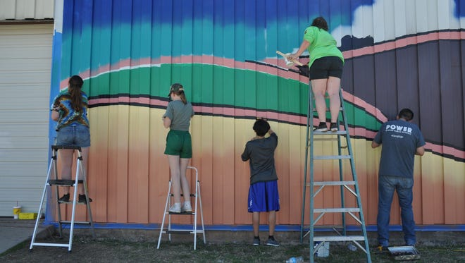 Students and staff from Grand Prairie Fine Arts Academy work on a mural at 301 Locust St. on March 24.