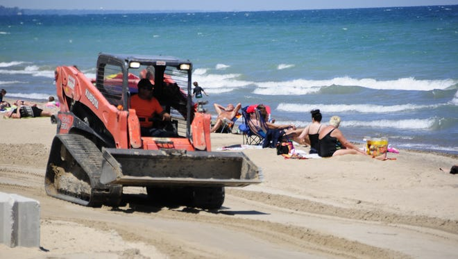 Alan Briolat uses a skid loader to renew the beach at Fort Gratiot County Park.