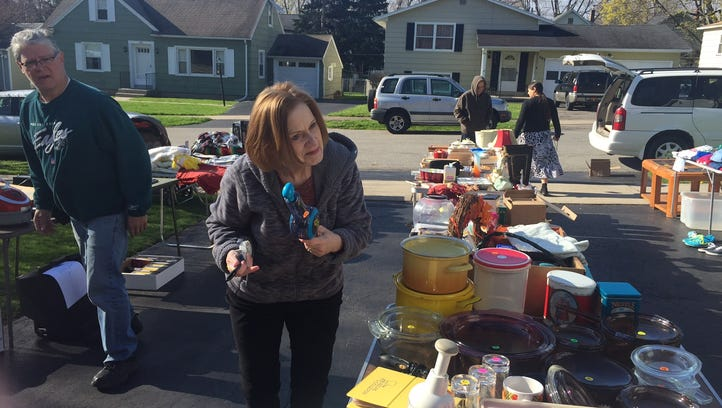 Debbie Mulcahy sets up her goods at a garage sale in Irondequoit on Saturday.