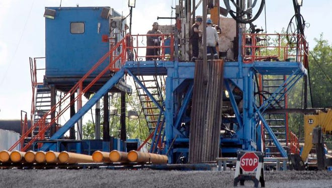 In this June 25, 2012, file photo, a crew works on a gas drilling rig at a well site for shale based natural gas in Zelienople, Pa. Such a sight is now unlikely in New York unless someone mounts a hefty legal challenge.