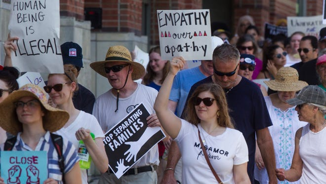 Community members hold signs during a Families Belong Together rally in Iowa City on Saturday, June 30, 2018. The march began on the west steps of the Old Capitol building and ended in College Green Park, one mile away where speakers addressed the crowd.