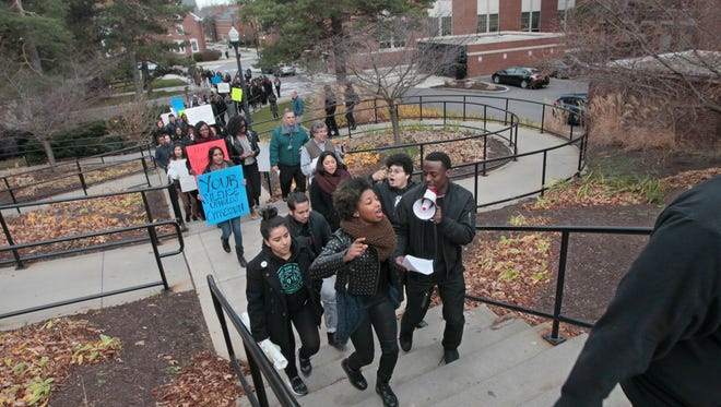 Senior Farid Adenuga, Brooklyn, with bullhorn, and sophomore Kavon Holley, lead student protesters as they march across campus.