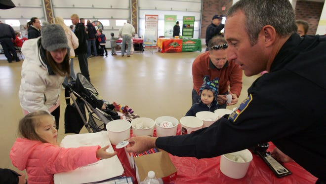 Germantown Police Officer Ray Borden gives Remy Lichtig a button she created during Germantown's 2014 Fire Safety Fair. This year's Fire Safety Fair will run from 10 a.m. to 3 p.m. Saturday, Oct. 7.