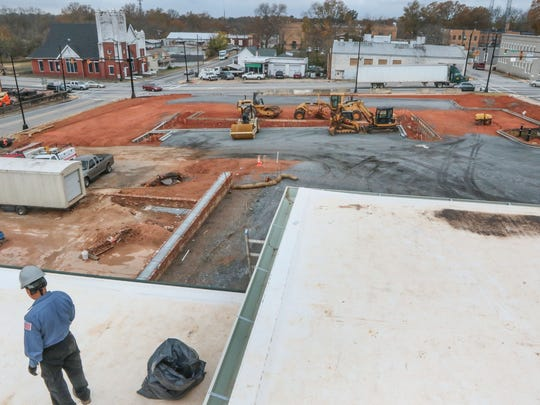 Julio Nino of Pickens Roofing works Wednesday near an unfinished parking lot at the Bleckley Station construction site in downtown Anderson.