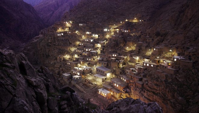 """Palangan Village, in the mountains near the Iraq border. Palangan, illustrative of many of the country's rural settlements, has benefitted handsomely from government support. Many villagers are employed in a nearby fish farm, or are paid members of the  Basij, whose remit includes prevention of """"westoxification"""", and the preservation of everything the 1979 islamic revolution and its leader the Ayatollah Khomeini stood for, including strict rules on female clothing and male/female interaction."""
