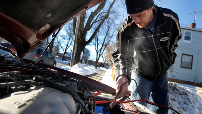Phil Hiles braves subzero temperatures to help jump-start a neighbor's car Jan. 7 in Appleton. While the temperatures will be brisk next week, overnight temperatures will remain in the teens.