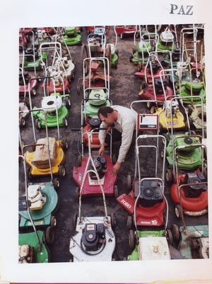 Don Carpenter of Carpenter's Saw Shop finishes the adjustments on one of many lawn mowers he has repaired in May of 1985.