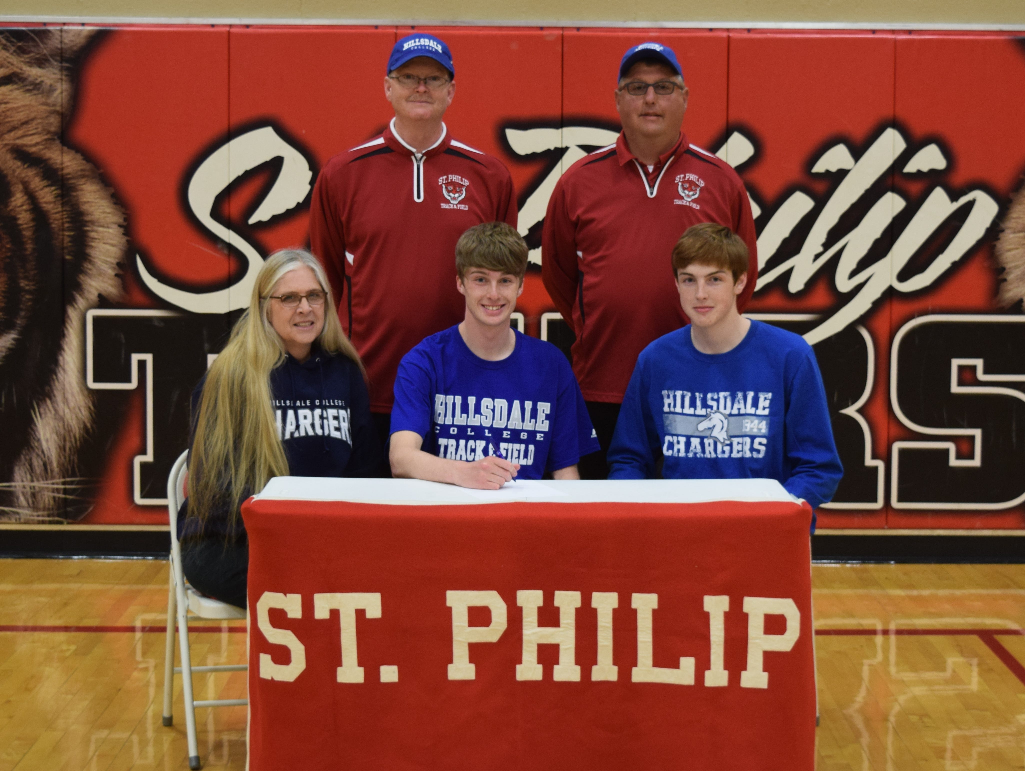 St. Philip senior David Downey signs his National Letter of Intent with the Hillsdale College men's track and field team, surrounded by parents Teresa Downey and Dave Downey, his brother JC Downey and St. Philip track coach Jeff Minier.