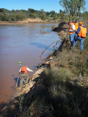 Surveyors from the Bureau of Land Management came onto Kevin Hunter's property along the Red River Monday morning to begin the determination of where his land ends and where government-owned land begins.