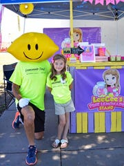 Aleese Haile is photographed with Mr. Lemonhead next to her award-winning lemonade stand during the 2017 Lemonade Day Wichita Falls event.