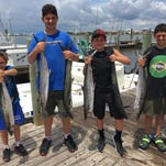 A group of happy youngsters after a day of king mackerel fishing around the USS Massachusetts with Captain Tyler Massey of Hot Spots Charters.