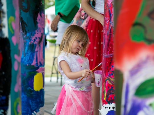 Amelia Boody, 3, of Jupiter, Fla., paints a totem at ArtFest in downtown Fort Myers on Saturday.