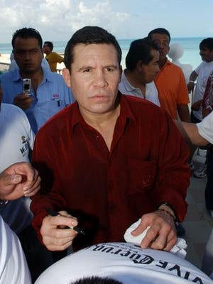 """Boxer Julio César Chávez signs an autograph for a fan in Cancun, Mexico, on Tuesda, Jan. 31, 2006, before the World Boxing Council, (WBC) """"Nights of Champions Event"""" which will included 86 champions from around the world."""