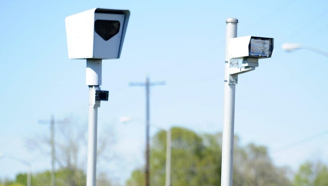 Traffic cameras monitor the intersection of Ambassador Caffery Parkway and Dulles Drive for potential red light and speeding violations in Lafayette, LA, Monday, March 31, 2014.