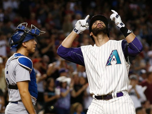 Arizona Diamondbacks' J.D. Martinez, right, points to the sky after hitting a home run as Los Angeles Dodgers' Austin Barnes, left, pauses at home plate during the fourth inning of a baseball game Thursday, Aug 10, 2017, in Phoenix. (AP Photo/Ross D. Franklin)