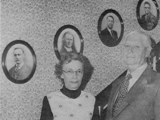 Alice and Vernon McAfee posed in front of portraits of, from left, Wade Alexander McAfee, Earl Thomas McAfee, Vernon as a younger man and his son, Tommy McAfee.