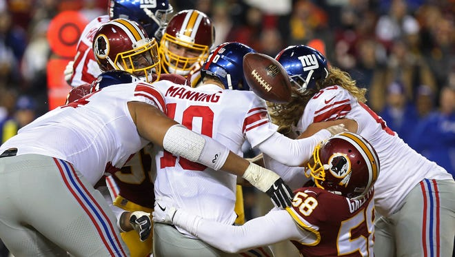 New York Giants quarterback Eli Manning (10) fumbles the ball while being sacked by Washington Redskins linebacker Junior Galette (58) and Redskins outside linebacker Ryan Kerrigan (91) in the fourth quarter at FedEx Field on Thursday, Nov. 23, 2017.