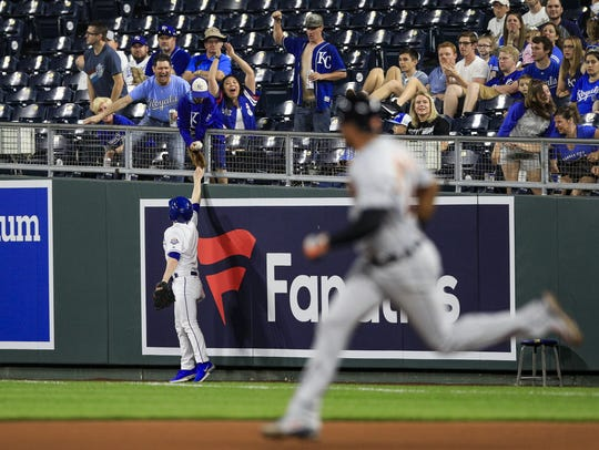 A Royals ball boy hands a live ball to fans that was