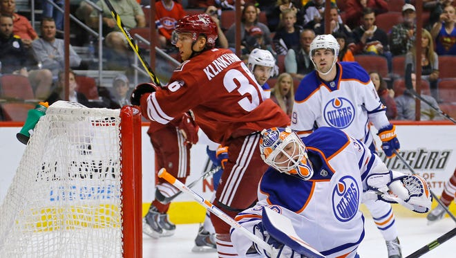 Arizona Coyotes left wing Rob Klinkhammer (36) slips the puck past Edmonton Oilers goalie Ben Scrivens (30) to score during the second period of their NHL game Wednesday, Oct. 15, 2014 in Glendale, Ariz.