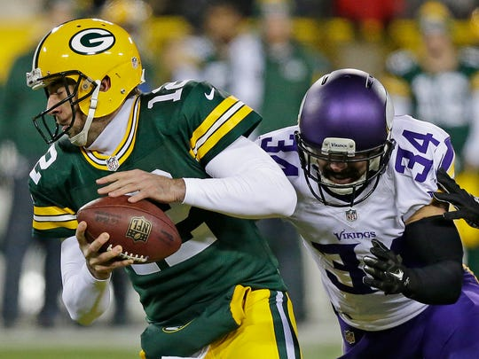 Green Bay Packers quarterback Aaron Rodgers (12) tries to avoid a hit in the back field by  Minnesota Vikings strong safety Andrew Sendejo (34) in the first quarter at Lambeau Field.