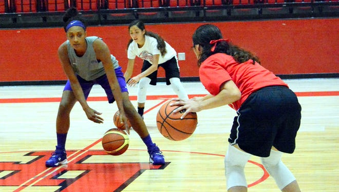 Professional women's basketball player Adrianne Ross teaches Loving how to improve on crossover dribbling on Wednesday.
