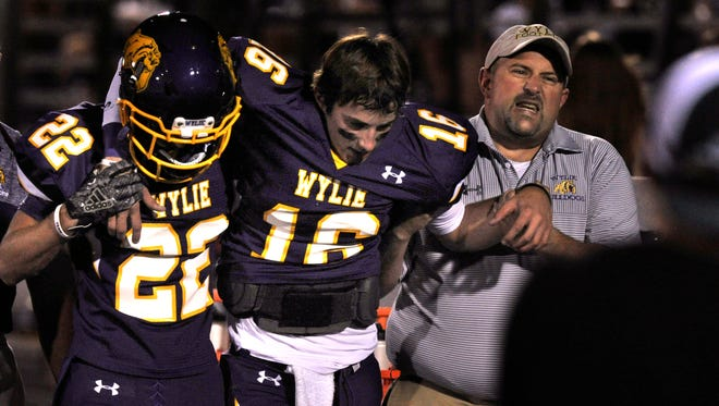 Wylie High School quarterback Sam King is helped along the sidelines Friday night Sept. 8, 2017 by teammate Hayden Murphy and team Trainer Brian Stuart. King appeared to have injured his knee but was back in action a few plays later.