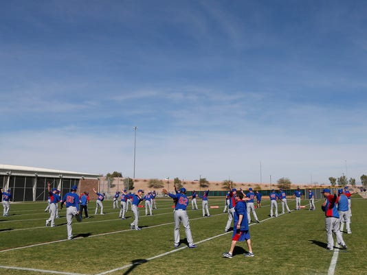 The Chicago Cubs pitchers and catchers stretch during the team's first spring training baseball practice, Friday, Feb. 14, 2014, in Mesa, Ariz. (AP Photo/Matt York)