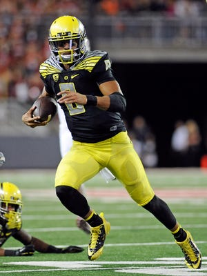 Oregon Ducks quarterback Marcus Mariota (8) scrambles out of the packet against the Washington State Cougars during the second half at Martin Stadium. The Ducks beat Cougars 38-31.