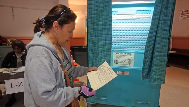Rose Valentin studies a sample ballot during Tuesday's school budget and trustee election, on her way to the voting booth at the Pennington school in Mount Vernon.