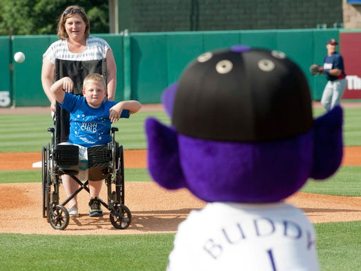 Robert Kenney, age 9, wheeled out to the mound by his mother, Patti, throws the honorary first pitch of the game to Louisville Bats' mascot, Buddy Bat as the Make A Wish Foundation is honored at Slugger Field. 06 July 2014