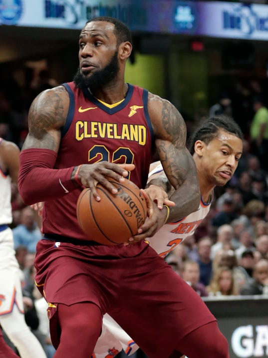 Cleveland Cavaliers' LeBron James, left, drives past New York Knicks' Trey Burke in the first half of an NBA basketball game, Wednesday, April 11, 2018, in Cleveland. (AP Photo/Tony Dejak)