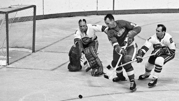 Oakland Seals goalie Charlie Hodge tries to shift across