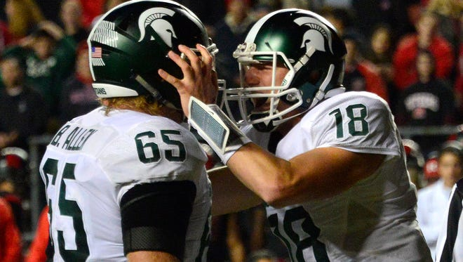 Michigan State quarterback Connor Cook (18) shouts and grabs the helmet of teammate Brian Allen after the Spartans scored the winning touchdown late against Rutgers. Against Michigan the following week. Allen allowed a sack that hampered an MSU drive late in the game.