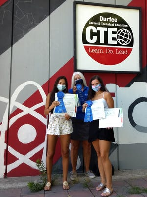 From left to right, Hannah Reitzas, teacher Susan Black and Faith Ferreria hold their ribbons and certificates at Durfee High School for winning an online STEM challenge.