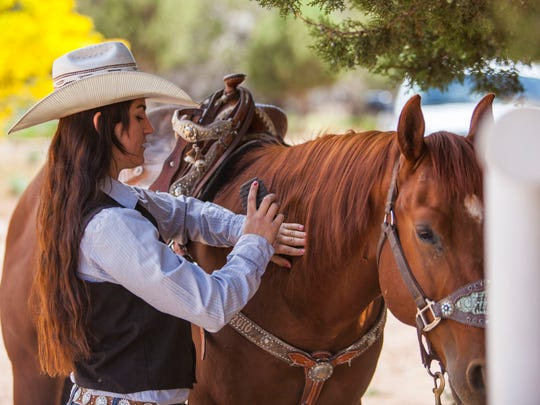 Tenille Rhodes brushes her horse, Boomer, at her home in Kanarraville last spring. She'll return to the College National Finals Rodeo this year.